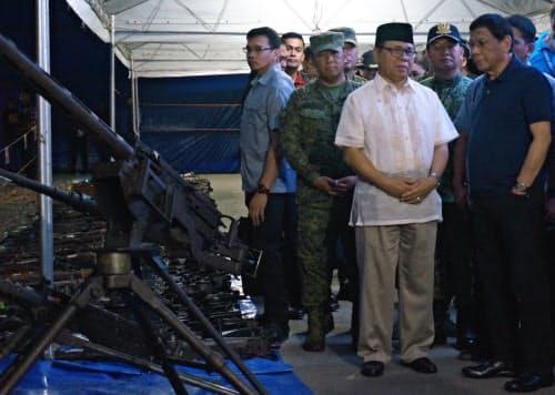 7日、フィリピンのイスラム武装勢力が提出した武器を見て回るドゥテルテ大統領(右)