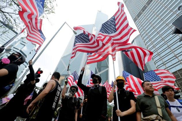米国旗を掲げ行進するデモ参加者(8日、香港)=ロイター