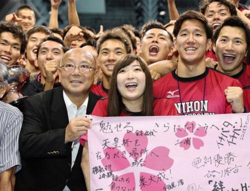 総合優勝した日本大の男子選手らと笑顔で記念写真に納まる池江璃花子選手=中央(8日、東京辰巳国際水泳場)=共同