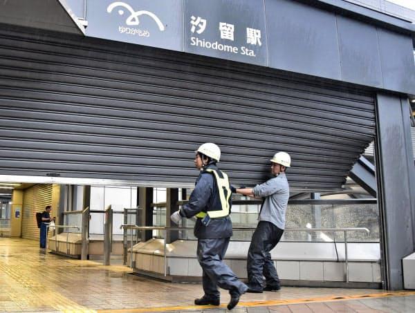 台風15号の影響で一部がめくれた、ゆりかもめ汐留駅のシャッター(9日午前、東京都港区)=共同