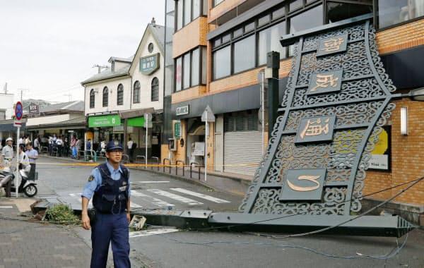 台風15号の影響で倒壊した商店街入り口の看板。左後方は鎌倉駅(9日午前、神奈川県鎌倉市)=共同