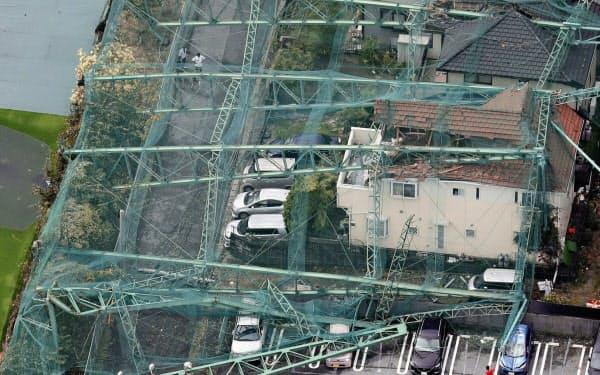 台風15号の影響でネットごと倒壊したゴルフ練習場のポール。住宅を直撃した(9日午前、千葉県市原市)=共同