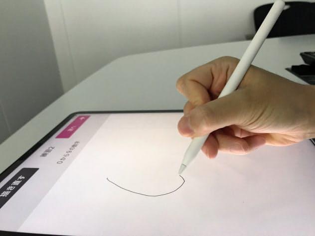 認知機能をみるため、端末上で簡単な図形や文字を書いてもらう(エーザイ提供)
