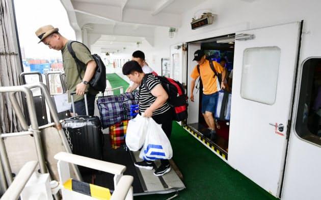 多くの荷物を抱えて新鑑真号から下船する乗客(8月、大阪市)