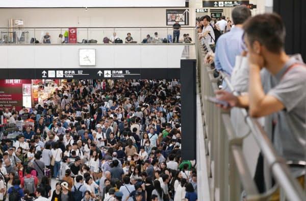混雑する成田空港の到着ロビー(9日夜)