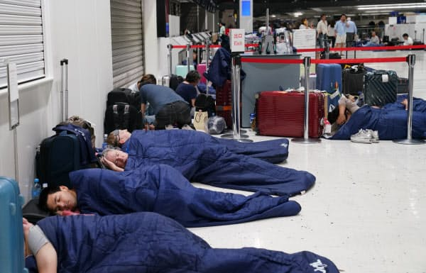 寝袋で一夜を過ごす成田空港の利用客(9日夜)