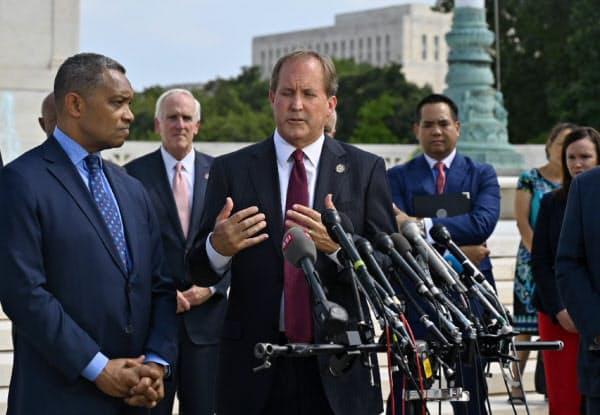 テキサス州のパクストン司法長官(中)らが9日、ワシントンの連邦最高裁前で会見してグーグルへの調査開始を発表した