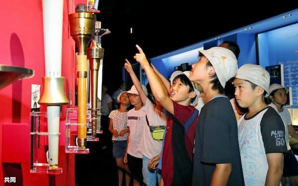 日本オリンピックミュージアムで過去大会の聖火のトーチを見る小学生(2日、東京都新宿区)=共同
