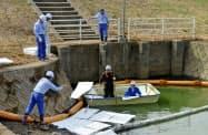 佐賀県大町町の水路に浮かんだ油を除去する国交省職員ら(10日)=共同