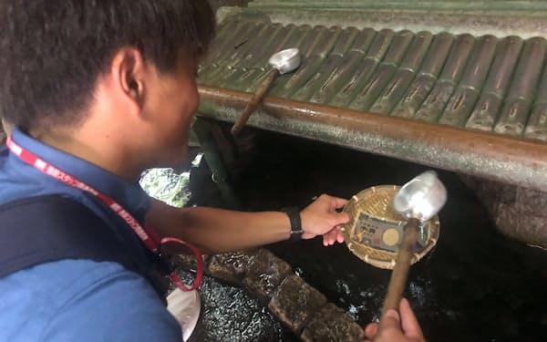 お金に水をかけることで、心身も清めてもらう(神奈川県鎌倉市)