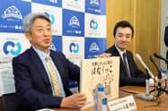 客に披露する紙芝居を手に説明する小国社長(左)と村上社長(11日、秋田県庁)