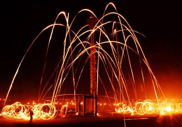高さ18メートルの灯籠木の傘めがけて勢いをつけたたいまつを周囲から投げ上げる(京都市左京区)