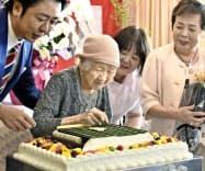 高島宗一郎市長(左)からオセロを模したケーキを贈られた田中カ子さん(11日、福岡市)=共同