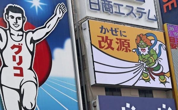 カイゲンファーマが9年ぶりに刷新した大阪・道頓堀にある屋外広告(右)=共同