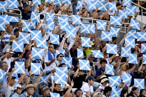 旗を掲げてラグビーW杯スコットランド代表を歓迎する人たち(11日、長崎市)=共同