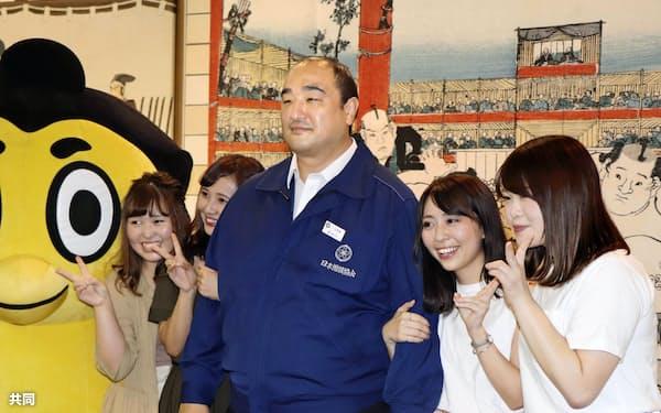 ファンと記念撮影に応じる安治川親方=中央(10日午後、東京・両国国技館)=共同
