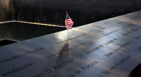 犠牲者の名前が刻まれた追悼施設に残されたアメリカの国旗=ロイター