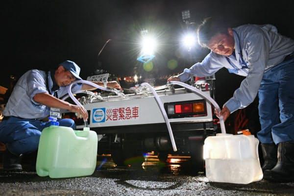 給水所となっている公民館で水をくみ出す職員(11日、千葉県君津市)