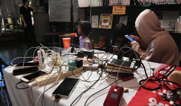 公民館で非常用電源から携帯電話に充電する人たち(11日、千葉県君津市)
