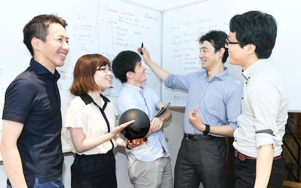 東京大学のシェアオフィス「FoundX」で、東大職員(右端)を交えて話すダイキン工業の社員ら(東京都文京区)
