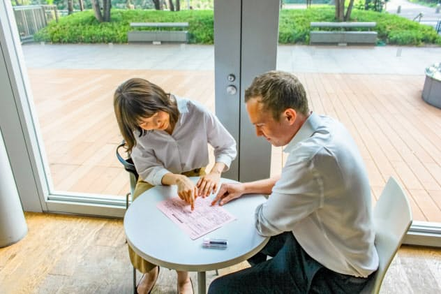 住民登録に必要な用紙の記入内容をガイドが翻訳して説明する