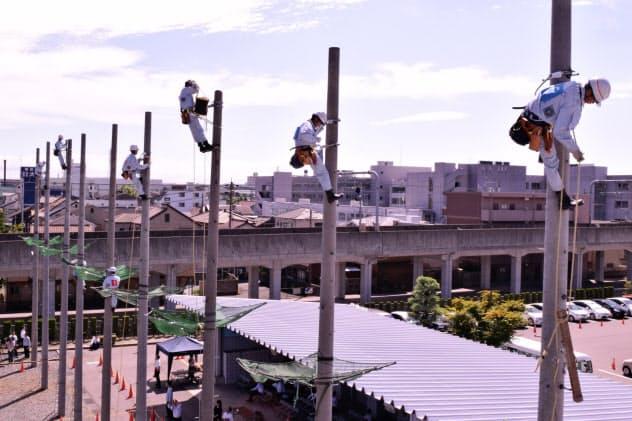 電柱の上で作業するトーエネックの新入社員(12日、名古屋市)