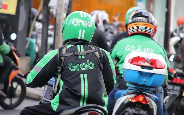 ジャカルタを走るグラブ(左)とゴジェックのバイク(4月)=三村幸作撮影