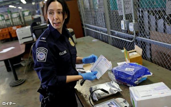 中国からの密輸を見つけるのは簡単ではない(シカゴの空港で小包の中身を検査する米税関の職員)=ロイター