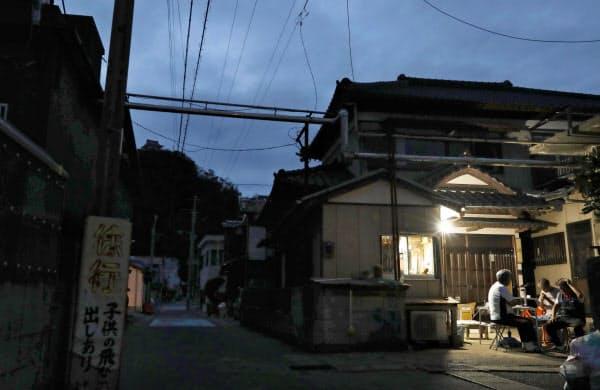 停電が続く千葉県鋸南町では、住民らが工面したガソリンと発電機でともした明かりに人々が集まっていた(12日夕)=共同