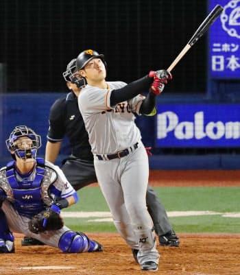 4回巨人1死、岡本が左越えに2者連続本塁打を放つ。捕手伊藤光(12日、横浜)=共同