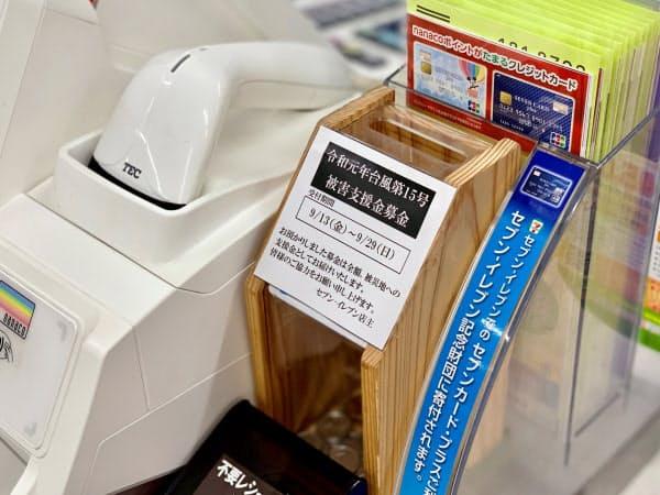 セブン―イレブンの店舗ではレジの横などに募金箱を置く(東京・千代田)