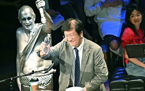 12日、イグ・ノーベル賞の授賞式で、5歳児の1日の唾液の分泌量に当たる500ミリリットルのペットボトルを掲げる明海大の渡部茂教授(米マサチューセッツ州ケンブリッジのハーバード大)=共同