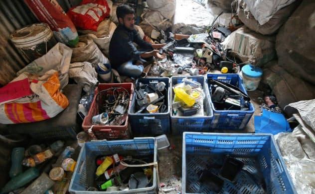 リサイクルのため、プラスチックごみの分別をする男性(ムンバイ)=ロイター
