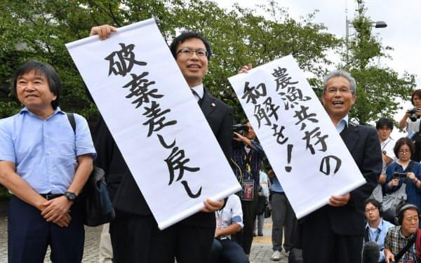 諫早湾干拓事業を巡る訴訟で、「破棄差し戻し」の紙を掲げる漁業者側(13日、最高裁前)