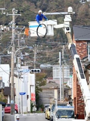 電線の復旧作業を進める作業員(13日、千葉県館山市)