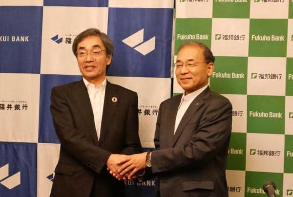 包括提携の記者会見を終え、握手する福井銀行の林頭取(左)と福邦銀行の渡辺頭取