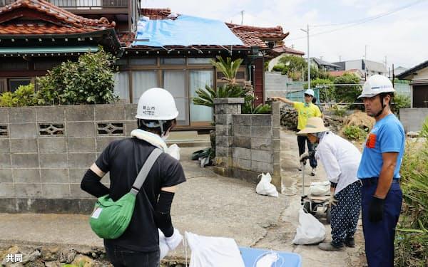 屋根に張るブルーシートを押さえる土のうを運ぶボランティアら(14日午前、千葉県館山市)=共同
