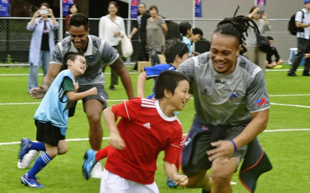 ラグビー教室で子どもたちと触れ合うサモア代表選手(14日、福島県いわき市)=共同