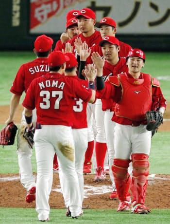 巨人に勝利し、タッチを交わす広島ナイン(14日、東京ドーム)=共同