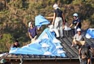 台風15号の被害にあった住宅で、ブルーシートなどを張る作業をする地元建設業者やボランティアの人ら(14日午後、千葉県館山市)=共同