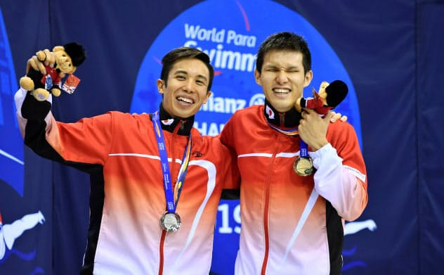 男子100メートルバタフライ(視覚障害S11)で獲得したメダルを胸に、笑顔で肩を組み記念写真に納まる金の木村敬一(右)と銀の富田宇宙(14日、ロンドン)=共同