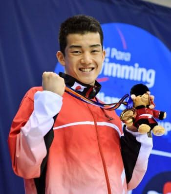 男子200メートル個人メドレー(知的障害)で優勝し、金メダルを手にポーズをとる東海林大(14日、ロンドン)=共同