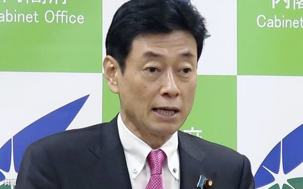 記者会見する西村経財相(12日、内閣府)
