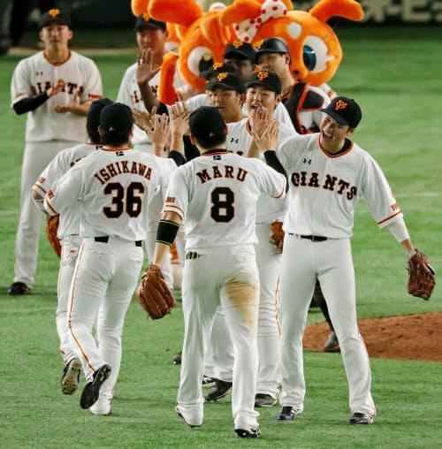阪神に逆転勝利、タッチを交わす巨人ナイン(15日、東京ドーム)=共同