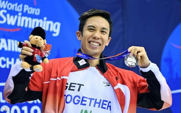 男子400メートル自由形(視覚障害S11)で銀メダルを獲得し、笑顔でポーズをとる富田宇宙(15日、ロンドン)=共同