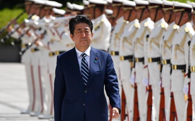 自衛隊高級幹部会同を前に栄誉礼を受ける安倍首相(17日、防衛省)