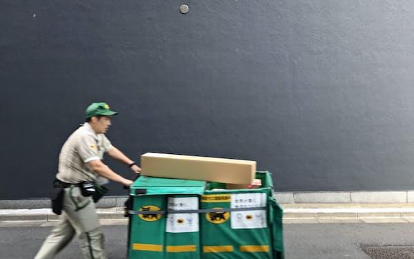 人件費上昇に業績の伸びが追いついていない(写真は荷物を配送するヤマト運輸の社員)