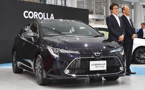発表された新型「カローラ ツーリング」と記念写真に納まるトヨタ自動車の吉田副社長(左)ら(17日、東京都江東区)