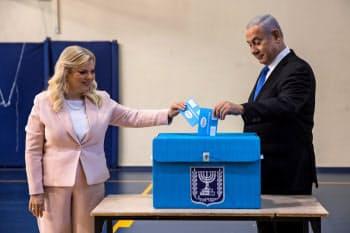 17日、夫人と共に票を投じるイスラエルのネタニヤフ首相(右)(エルサレム)=ロイター