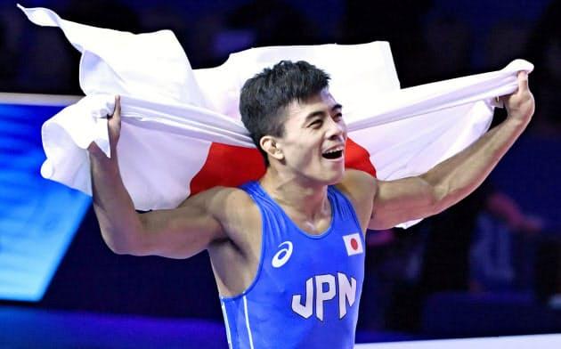 男子グレコローマン60キロ級で優勝し、日の丸を背に喜ぶ文田健一郎=共同